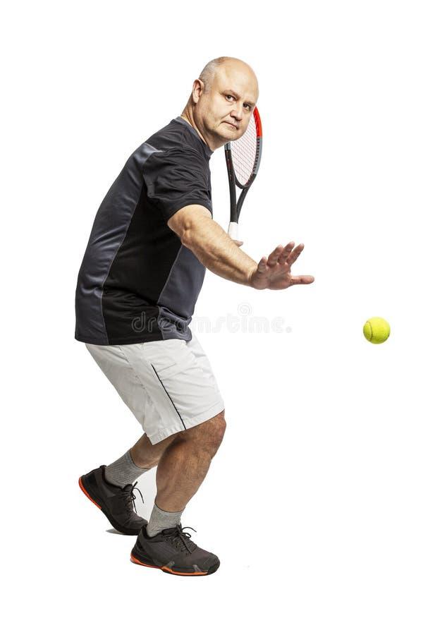 Un hombre calvo de mediana edad juega a tenis zurdo Aislado en un fondo blanco fotografía de archivo