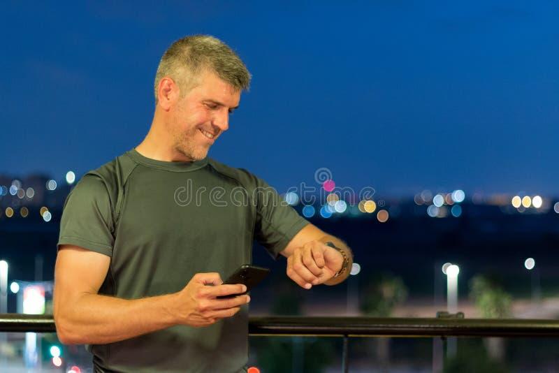 Un hombre canoso después de correr estudios los datos de entrenamiento sobre su reloj y teléfono móvil imagenes de archivo