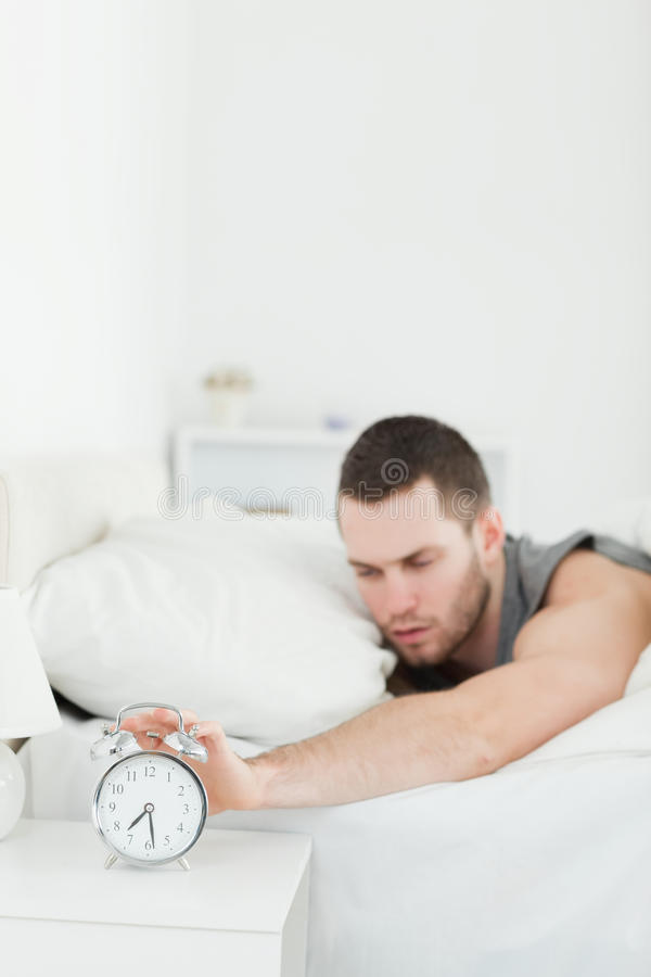 Un hombre cansado que es despertado por un reloj de alarma fotos de archivo libres de regalías