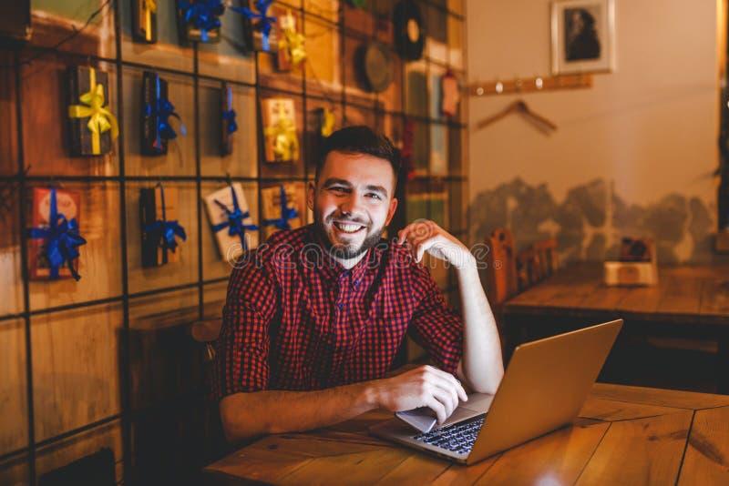 Un hombre caucásico hermoso joven con la barba y la sonrisa dentuda en camisa a cuadros roja está trabajando detrás del ordenador imágenes de archivo libres de regalías
