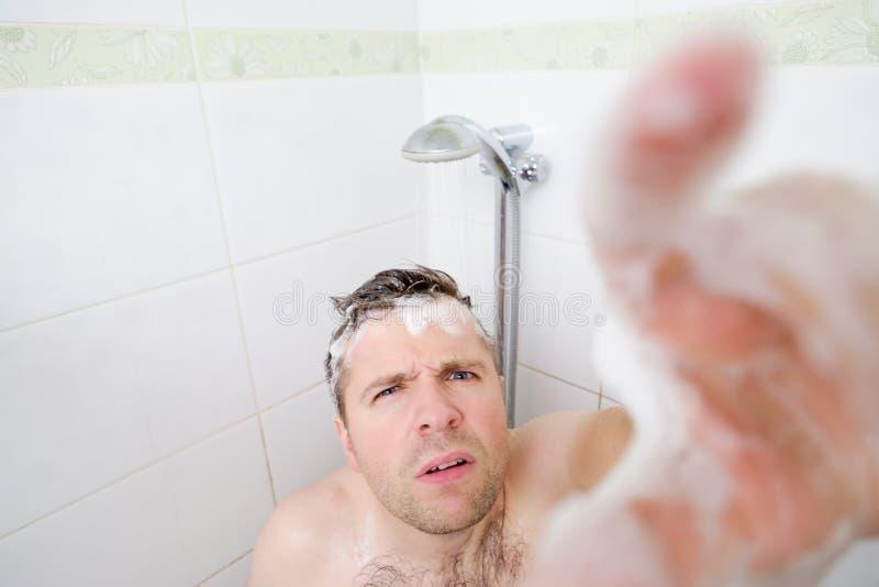 Un hombre caucásico joven toma una ducha y nota una cámara ocultada fotografía de archivo libre de regalías