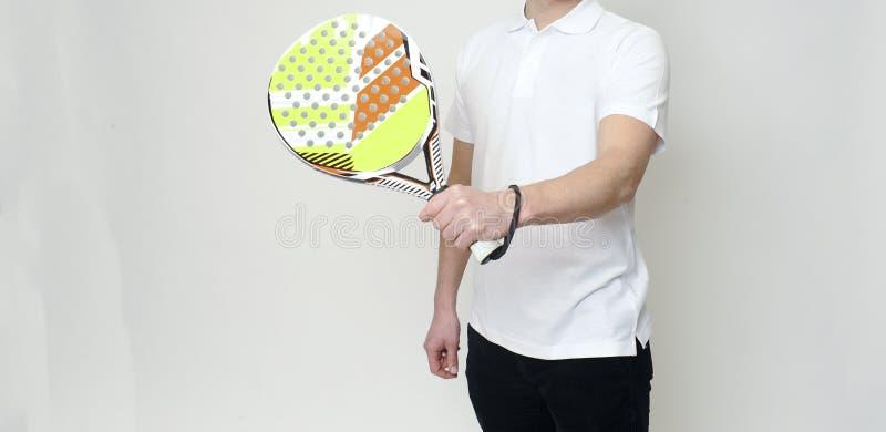 Un hombre caucásico que juega al jugador de tenis de Padel aislado en el fondo blanco foto de archivo