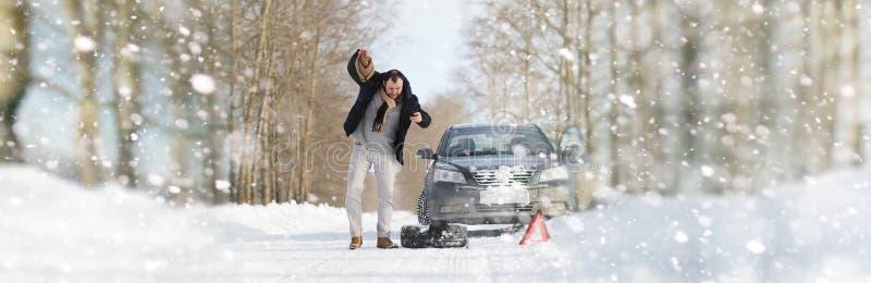 Un hombre cerca de un coche quebrado en un día de invierno foto de archivo