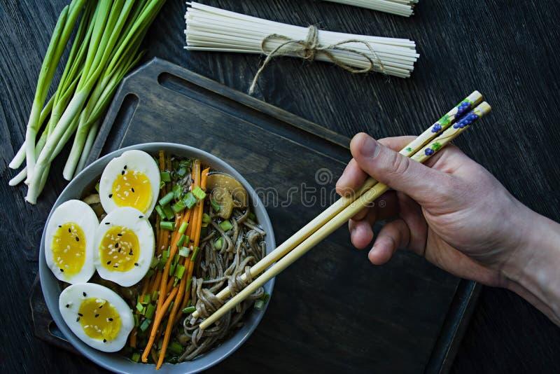 Un hombre come los tallarines del soba del alforfón con la salsa y los acompañamientos en caldo Comida japonesa Cocina asi?tica F fotos de archivo libres de regalías