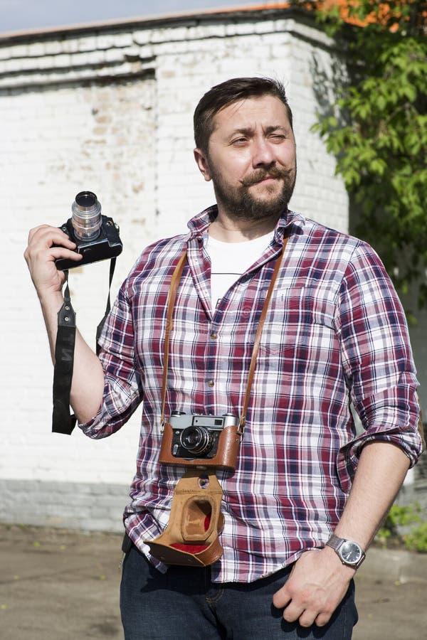 Un hombre con dos cámaras contra una pared de ladrillo blanca fotografía de archivo