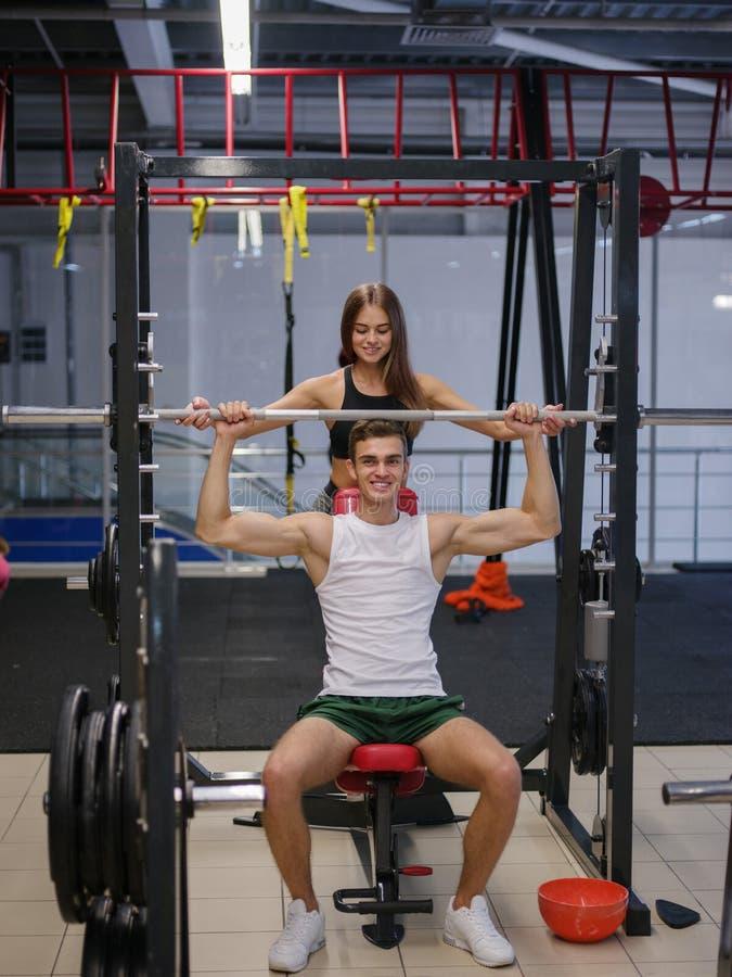 Un hombre con el cuerpo atlético hermoso que hace ejercicios con un barbell en un fondo del gimnasio aptitud, concepto del levant foto de archivo libre de regalías