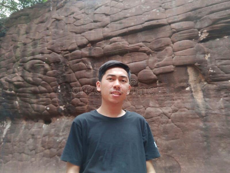 Un hombre con el fondo grande de la pared de piedra fotografía de archivo