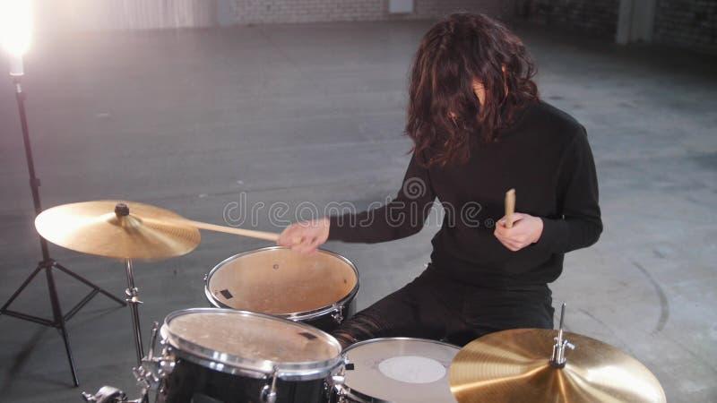 Un hombre con el pelo largo que juega los tambores y los sistemas el ritmo imagen de archivo