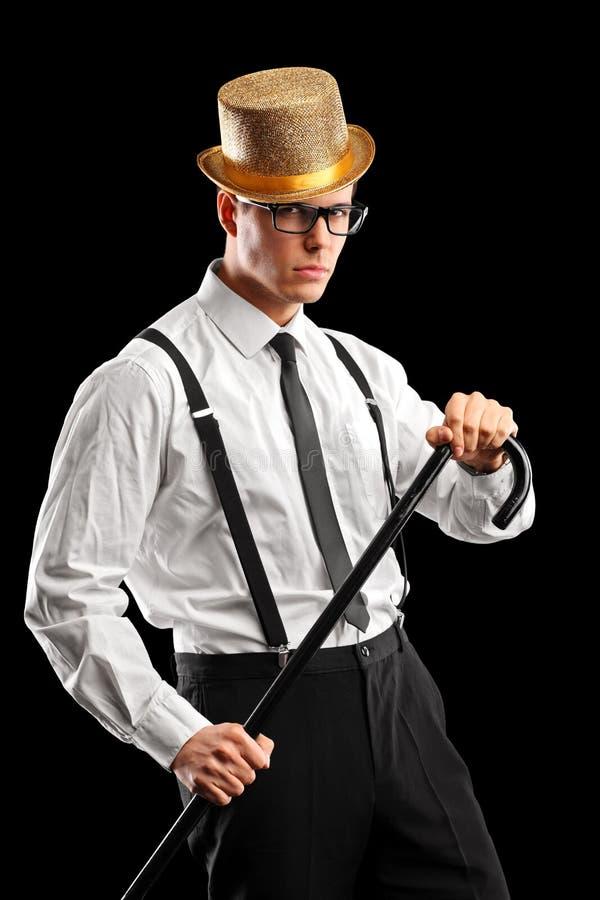 Un hombre con estilo con el sombrero que sostiene un bastón imágenes de archivo libres de regalías