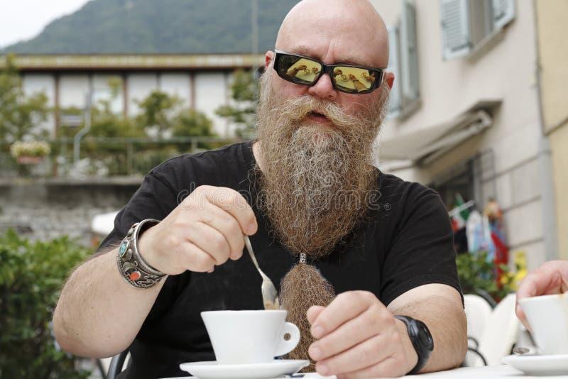un hombre con la barba larga, bebiendo, goza de una taza de café, Cappucino foto de archivo libre de regalías