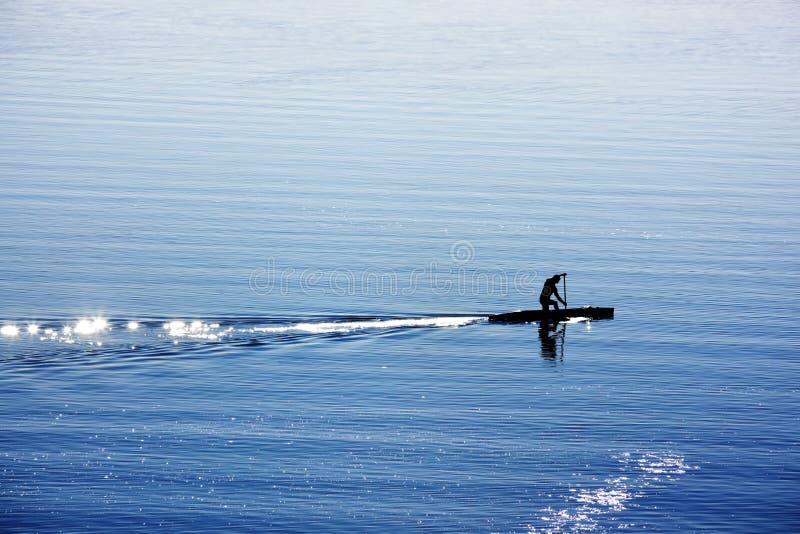 Un hombre con la canoa en el lago fotografía de archivo libre de regalías