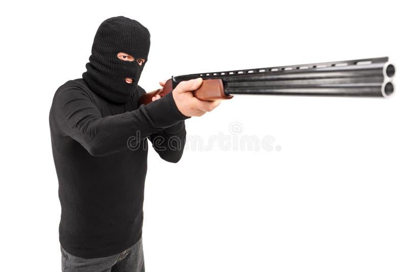 Un hombre con la máscara del robo que ataca alguien con la escopeta fotos de archivo libres de regalías