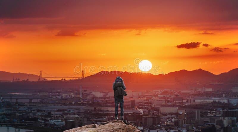 Un hombre con la mochila que se coloca en la montaña que disfruta de la opinión hermosa de la puesta del sol en la ciudad de Os imágenes de archivo libres de regalías