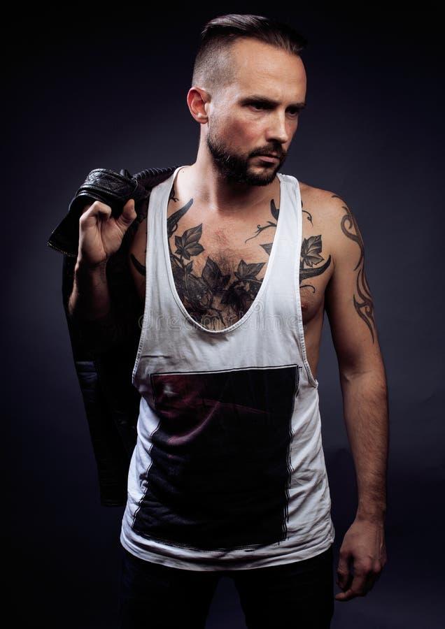 Un hombre con los tatuajes en sus brazos Silueta del cuerpo muscular individuo brutal caucásico del inconformista con el corte de fotografía de archivo