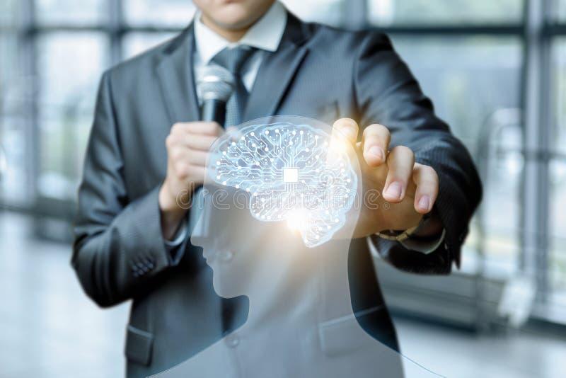 Un hombre con un micrófono en su mano está tocando un jefe de una figura transparente con el modelo digital brillante del cerebro fotos de archivo libres de regalías