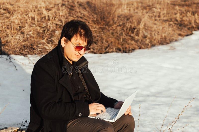 Un hombre con un ordenador portátil en la calle imágenes de archivo libres de regalías