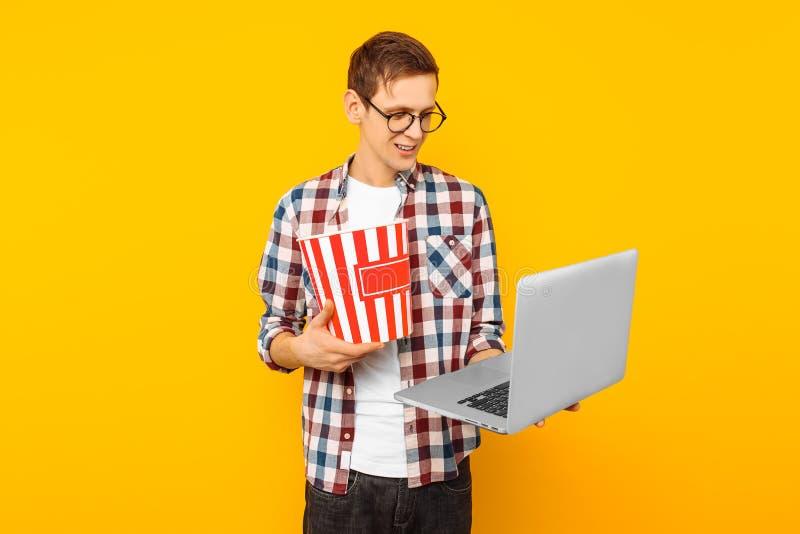 Un hombre con palomitas y un ordenador portátil en un fondo amarillo imagen de archivo