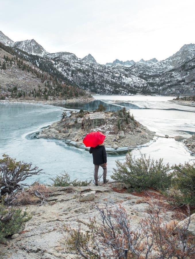 Un hombre con un paraguas rojo en el lago foto de archivo