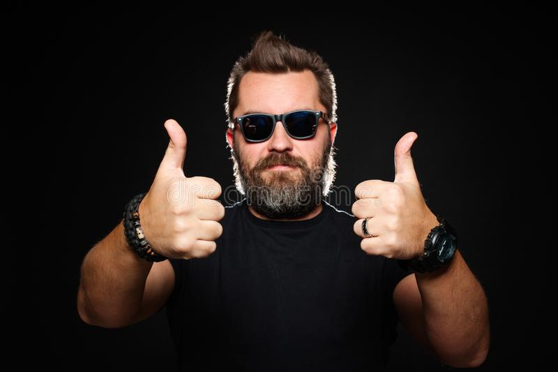 Un hombre con un peinado elegante y una barba hermosos, fuertes muestra dos pulgares para arriba en el estudio en un fondo negro  imagen de archivo libre de regalías