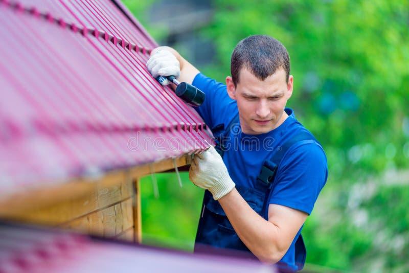 Un hombre con reparaciones de un martillo el tejado de una casa fotos de archivo