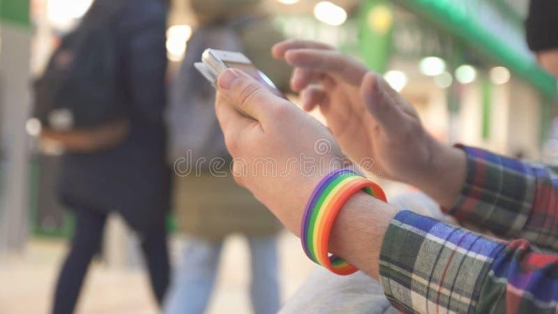 Un hombre con un símbolo de LGBT que lleva una pulsera utiliza un teléfono en un centro comercial foto de archivo