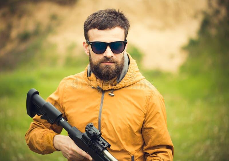 Un hombre con un rifle automático imagen de archivo libre de regalías