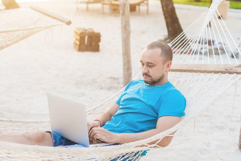 Un hombre con una barba que miente en una hamaca con un ordenador portátil y miradas en imágenes de archivo libres de regalías