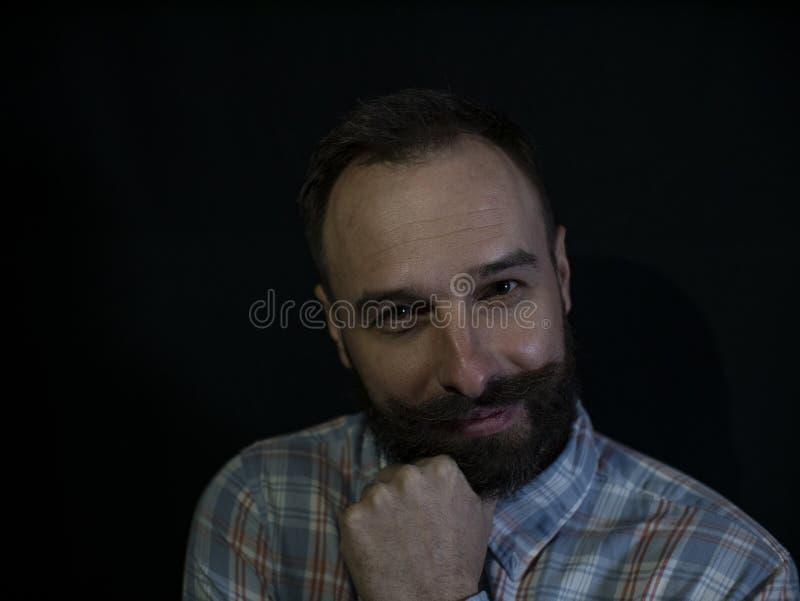 Un hombre con una barba y bigote con una cara astuta pensativa en un fondo negro imágenes de archivo libres de regalías