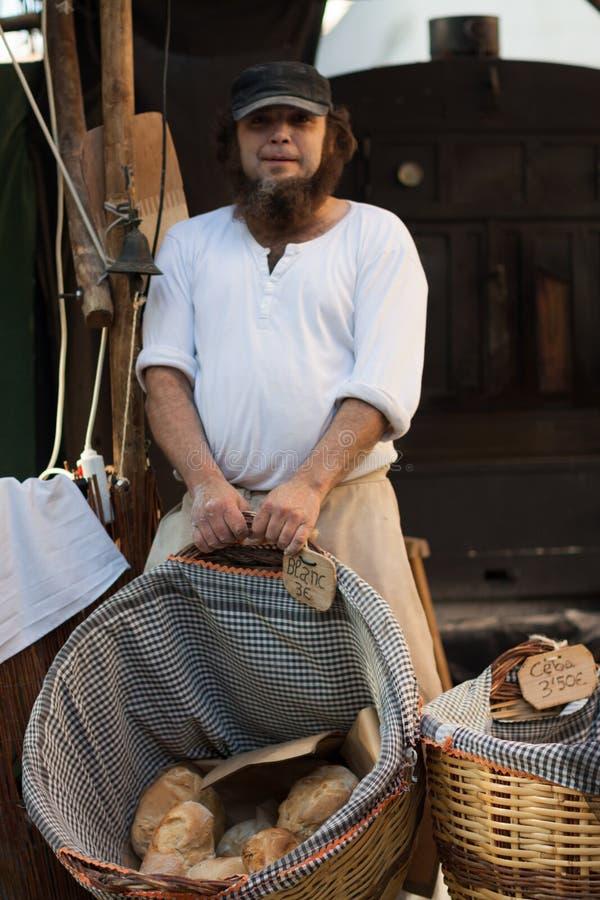 Un hombre con una cesta con pan fotos de archivo