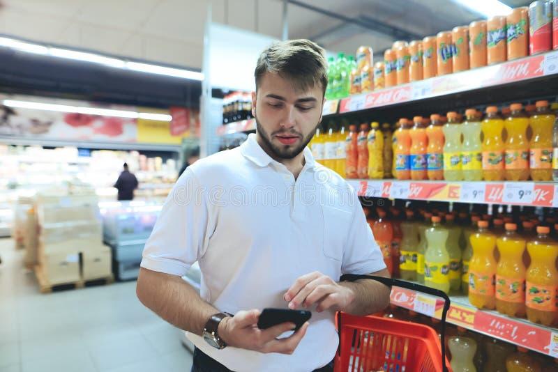 Un hombre con una cesta mira el teléfono mientras que hace compras en un supermercado El hacer compras en la tienda fotografía de archivo libre de regalías