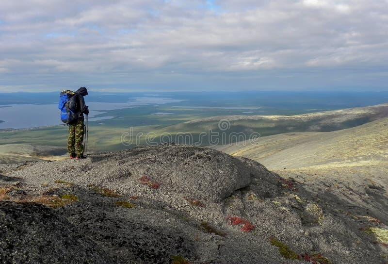 Un hombre con una mochila azul de la parte posterior en las montañas imagen de archivo