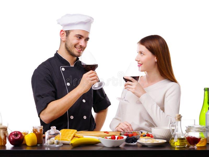 Un hombre con una mujer en la cocina, con los vidrios de vino en sus manos fotografía de archivo libre de regalías
