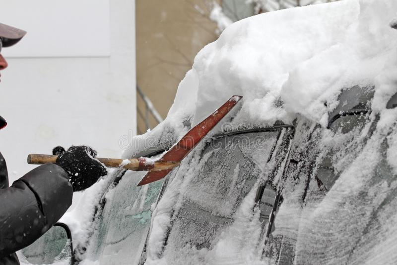 Un hombre con una pala del metal limpia el coche de nieve en la calle después de nevada grande en la ciudad, todos los coches deb foto de archivo libre de regalías