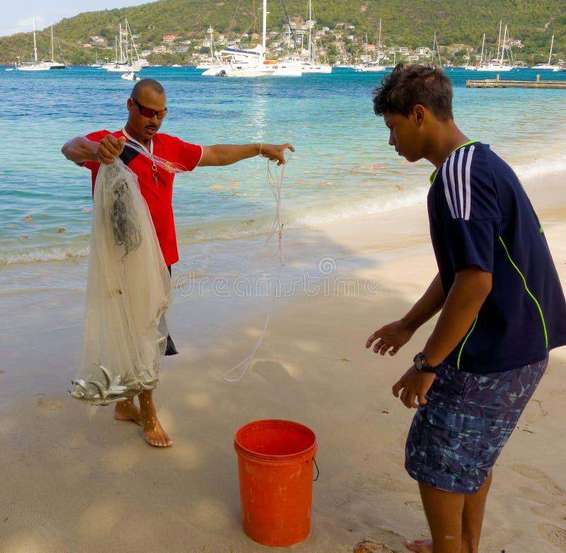 Un hombre con una red de pesca en el Caribe fotos de archivo libres de regalías