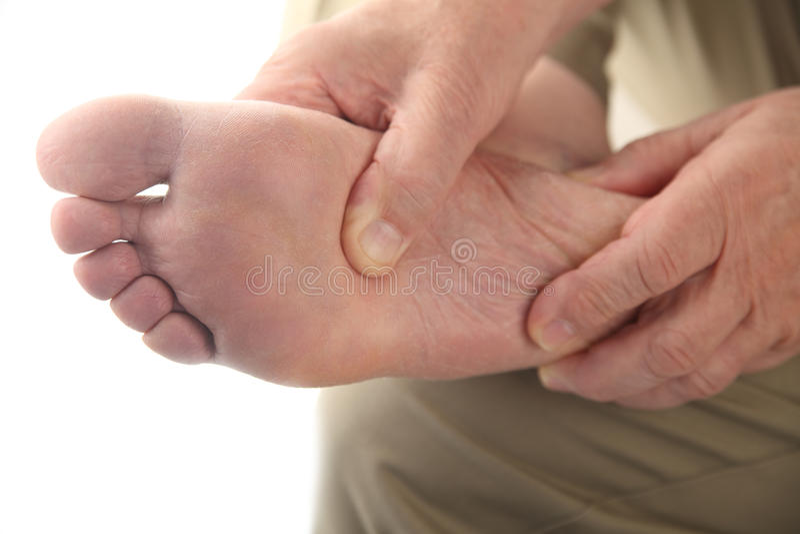Un hombre controla su pie de dolor foto de archivo libre de regalías