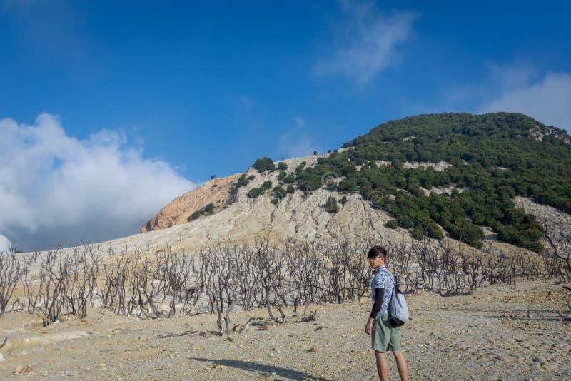 Un hombre coreano joven está disfrutando de la belleza de la montaña de Papandayan La monta?a de Papandayan es una del lugar pref fotos de archivo