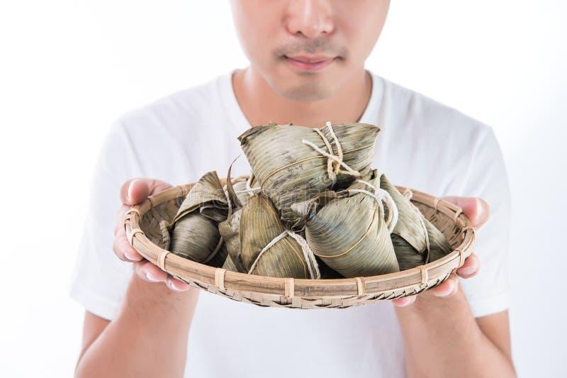 Un hombre de Asia está mirando Zongzi o la bola de masa hervida del arroz con la cara divertida y la sonrisa y está sintiendo int imagen de archivo libre de regalías