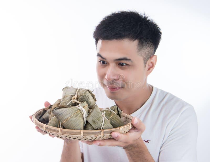 Un hombre de Asia está mirando Zongzi o la bola de masa hervida del arroz con la cara divertida y la sonrisa y está sintiendo int foto de archivo