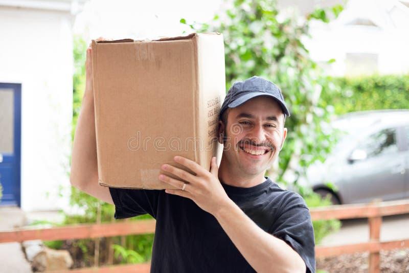 Un hombre de entrega con un bigote prominente y un sombrero azul que entregan una caja marrón genérica en una casa imagen de archivo
