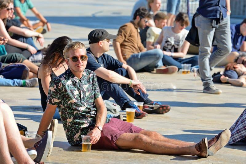 Un hombre de la audiencia mira un concierto y tiene una cerveza que se sienta en el piso imagen de archivo