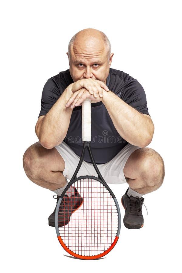 Un hombre de mediana edad calvo con posiciones en cuclillas de una estafa de tenis Aislado en un fondo blanco imagen de archivo libre de regalías