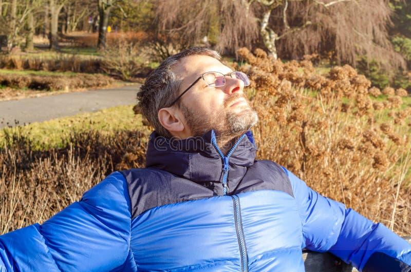 Un hombre de mediana edad con chaqueta baja se baña en el parque imagen de archivo