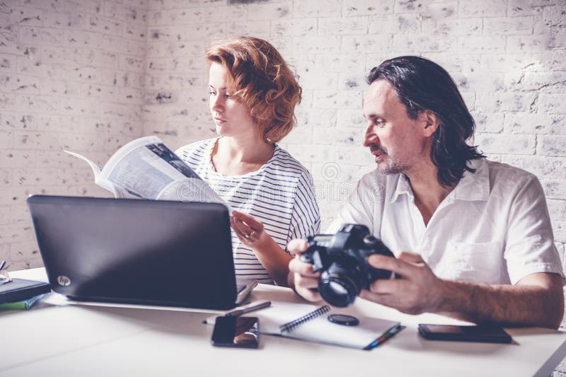 Un hombre de mediana edad y una mujer joven se están sentando en una tabla con imagenes de archivo
