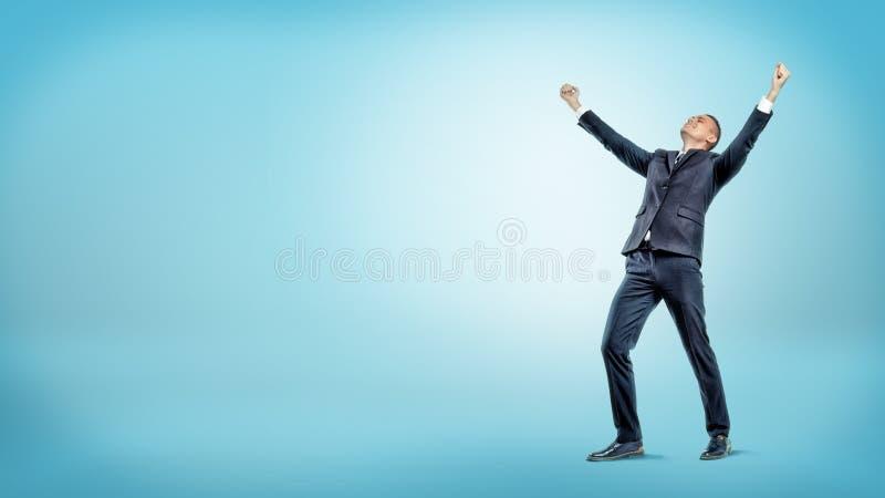 Un hombre de negocios alegre que se colocaba con las manos aumentó en la victoria y la mirada para arriba en fondo azul foto de archivo