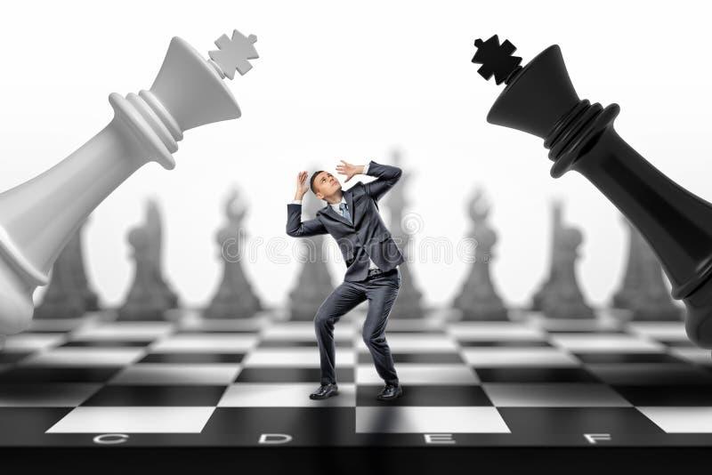 Un hombre de negocios asustado se coloca entre reyes negros y de un ajedrez del blanco que caen en él foto de archivo libre de regalías