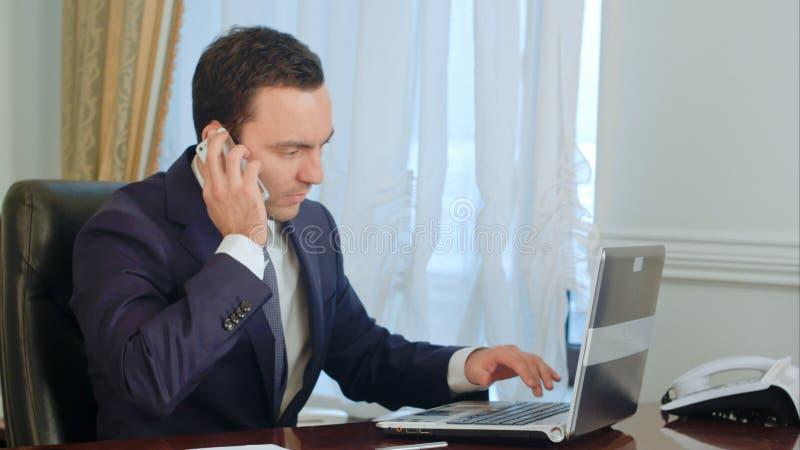Un hombre de negocios atractivo joven que trabaja en su escritorio, toma una llamada de teléfono, hace las notaciones, bebiendo e fotografía de archivo libre de regalías