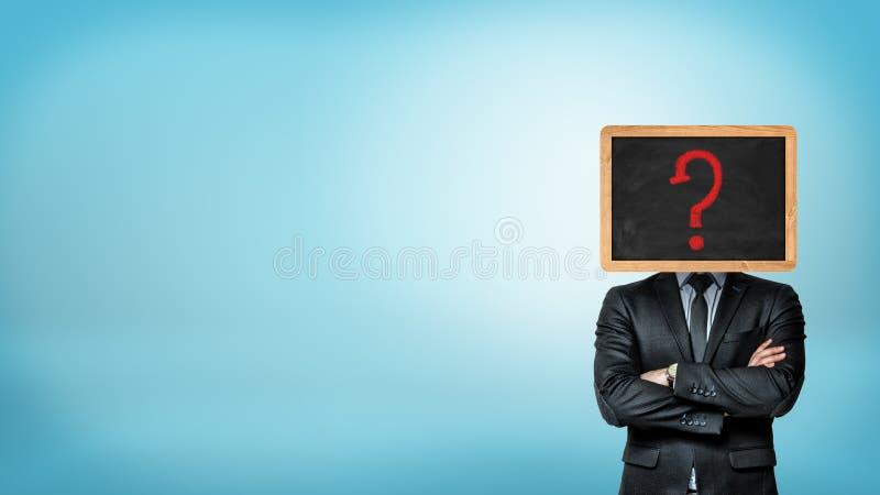 Un hombre de negocios con las manos cruzadas hace su cabeza substituir por una pequeña pizarra por un dibujo rojo del signo de in foto de archivo libre de regalías