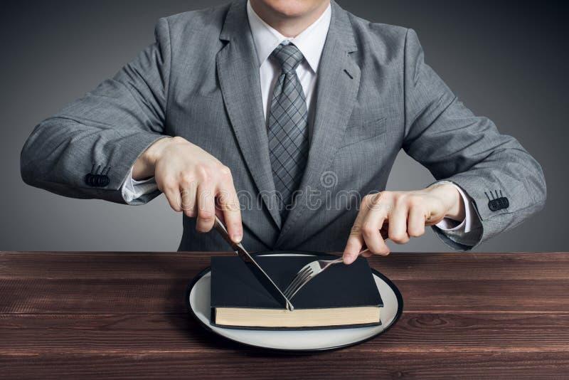 Un hombre de negocios con una bifurcación y un cuchillo come un libro en una placa El concepto de educación, desarrollo profesion foto de archivo