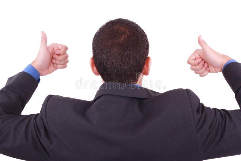 Un hombre de negocios da los pulgares para arriba (posterior) imagen de archivo