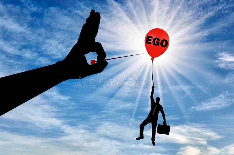 Un hombre de negocios egoísta se aferra en un globo llamado el ego y una mano grande con una aguja se prepone estallarla stock de ilustración